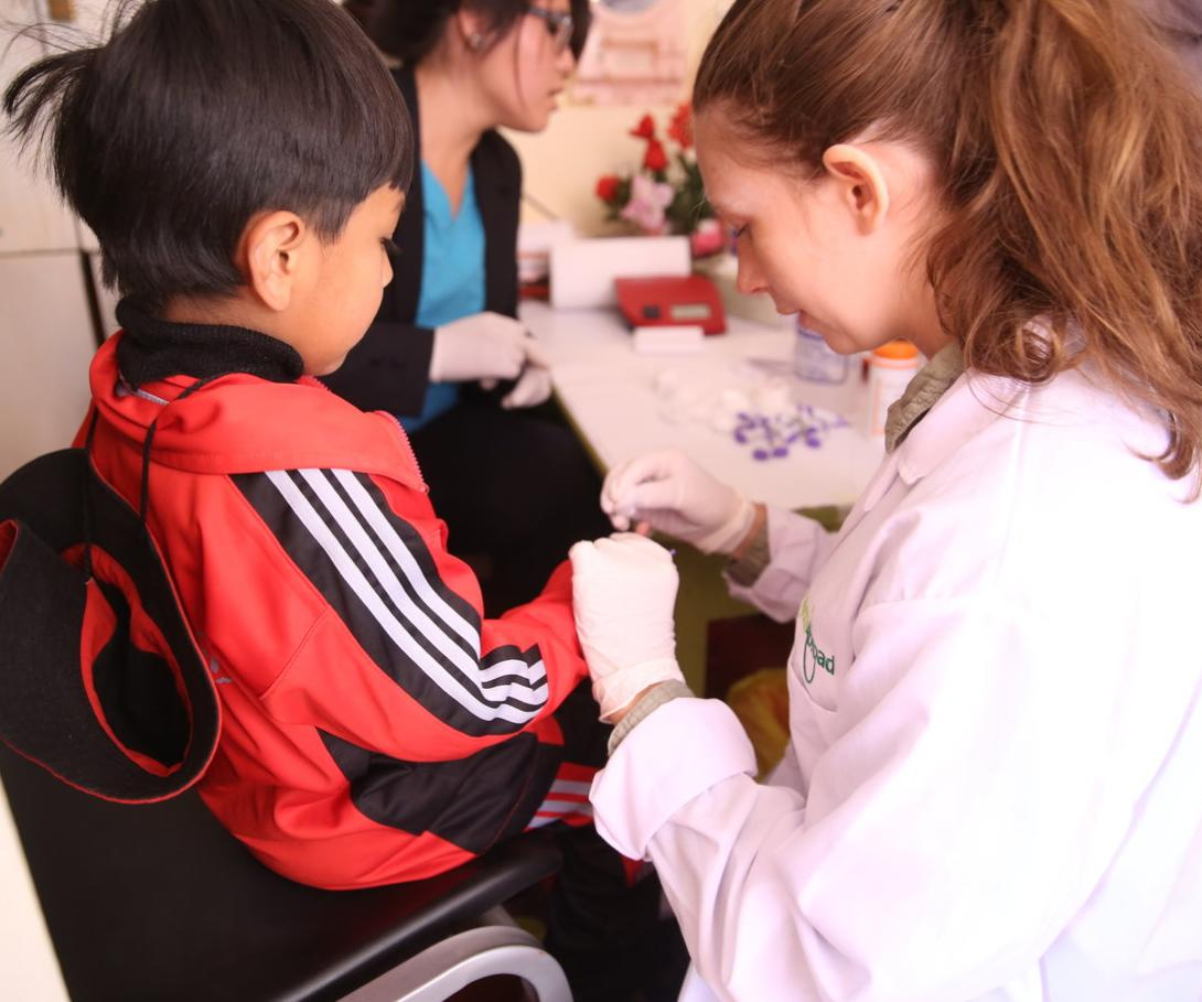 A young woman on a medical volunteer opportunity in South America checks blood sugar levels in Peru.
